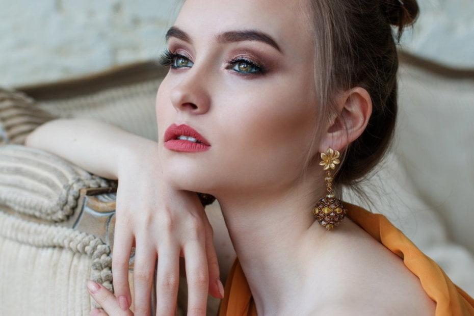 Moteris dėvinti auksinius auskarus